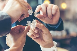 Businessman team work holding two jigsaw connecting couple puzzle piece for matching to goals target success and start up new project in office select focus Business Concept